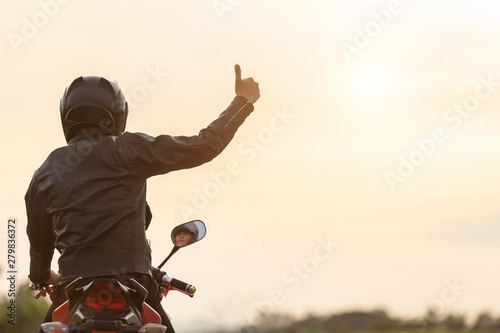 Fotografia Handsome motorcyclist wear leather jacket and holding helmet on the road