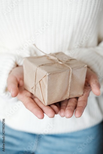Fotografía  Woman in white knitted sweater giving wrapped gift