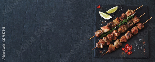 Delicious kebabs with spices. Kebab on wooden sticks. Fototapet