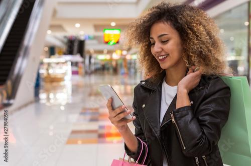 Fototapeta Cheerful african american girl having chat on cellphone obraz