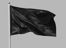 Black Flag Waving In The Wind On Flagpole, Isolated On Gray Background, Closeup