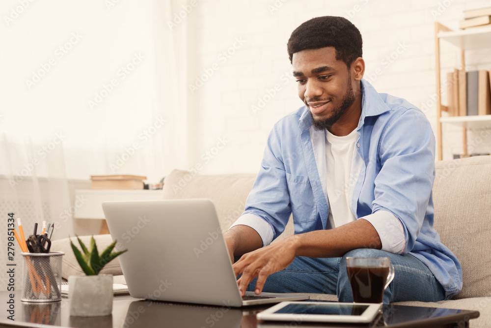 Fototapety, obrazy: Millennial black man working on laptop in home office