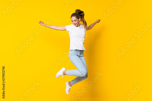 Young woman jumping over isolated yellow wall Fototapeta