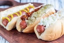 Three Varieties Of Hot Dogs Over A Cutting Board. One With Coleslaw, One With Pickle Relish And  Chilli And One Plain One With Mustard Only. Selective Focus With Blurred Background.