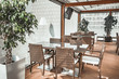 canvas print picture Attractive transparent glass terrace of the modern restaurant. Stylish interior the wicker tables and comfortable chairs in beige shades. Fashionable Mediterranean style.