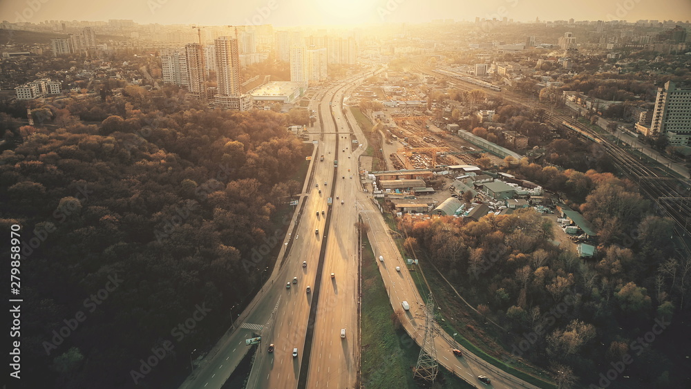 Fototapeta Urban Car Road Traffic Congestion Aerial View. City Street Motion Lane, Drive Navigation Overview. Busy Cityscape Speed Route with Forest Park Around. Travel Concept Drone Flight Shot