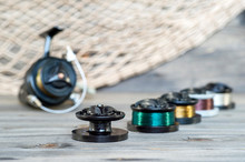Set With Multi-colored Spools With Fishing Line For Fishing On The Background Of Spinning Reels On Wooden Background.