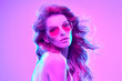 canvas print picture - High fashion. Woman in colorful bright Neon purple light. Glamour sexy disco girl with Trendy pink hair, Stylish sunglasses, makeup. Creative fashionable neon portrait. Night Club concept
