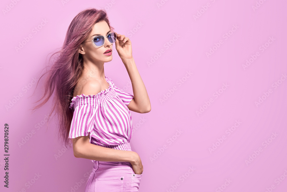 Fototapeta Fashion portrait Enchanting woman with trendy hairstyle, make up in stylish purple Outfit. Beautiful sensual long-haired slim model Girl in Trendy fashionable Sunglasses posing on purple.