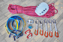 Concept For Packing Sport Climbing Gear For A Trip. Helmet, Rope, Harness, Belay Device, Carabiners, Quickdraws On Wooden Background.