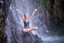 Young Woman With Open Arms In Lotus Position Under Waterfall In Tropical Nature. Wellness Spa And Yoga Meditation Concept In Holiday Nature.