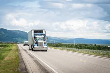 Trucking 18 wheeler on highway road in mountain landscape
