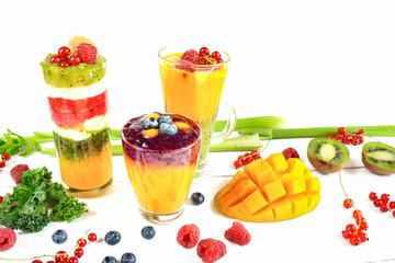 Wielowarstwowe smoothie w szklankach, wokół rozsypane owoce