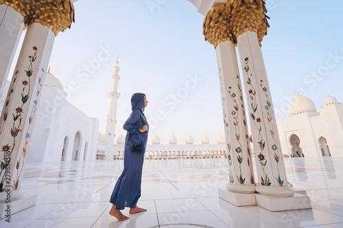 Foto auf Leinwand Abu Dhabi Traveling by Unated Arabic Emirates. Woman in traditional abaya standing in the Sheikh Zayed Grand Mosque, famous Abu Dhabi sightseeing.