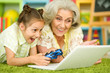 canvas print picture - granny with her granddaughter playing computer game