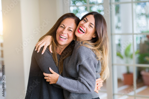 Fototapeta Beautiful family of mother and daughter together, hugging and kissing at home obraz