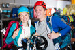 Laughing couple is choosing travel gear in shop