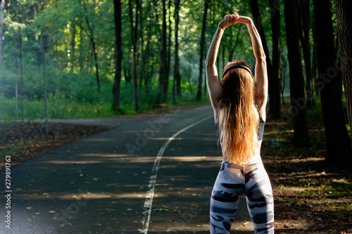 Athletic sporty and attractive girl resting and stretching after jogging and listening to music Fototapet