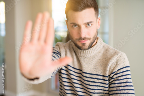 Young handsome man at home with open hand doing stop sign with serious and confi Fototapeta