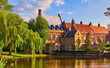 canvas print picture - Vintage building over lake of love in Minnewater park in Bruges Belgium near Beguinage monastery of Beguines. Picturesque landscape with green trees sunset time.