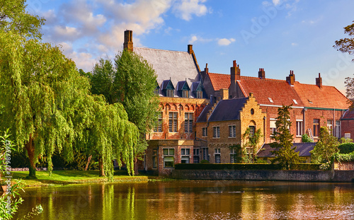 Vintage building over lake of love in Minnewater park in Bruges Belgium near Beguinage monastery of Beguines Wallpaper Mural