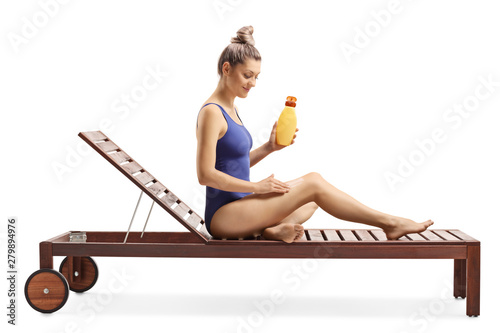 Tela Young woman applying a suncream and stting on a sunbed