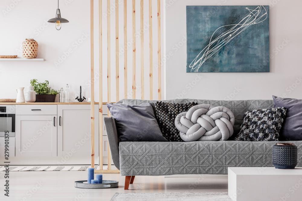 Fototapeta Trendy knot light grey pillow on comfortable scandinavian couch
