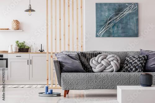 Trendy knot light grey pillow on comfortable scandinavian couch - 279901375