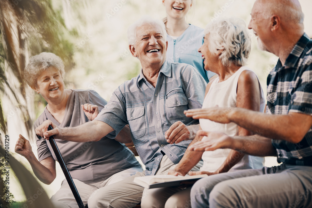 Fototapety, obrazy: Happy elderly man with walking stick and smiling senior people relaxing in the garden