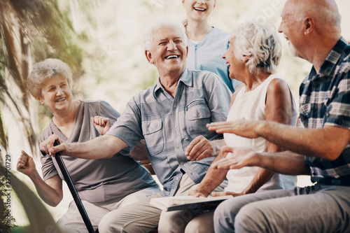 Fotografía Happy elderly man with walking stick and smiling senior people relaxing in the g
