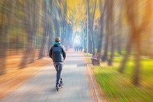 Young Adult Person Riding Modern Electric Scooter Along Beautiful Colorful Autumn City Park. Man Driving Gadget Vehicle Through Multicolored Fall Tree Valley. Motion Blur