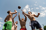 four sexy shirtless sportsmen playing basketball under blue sky
