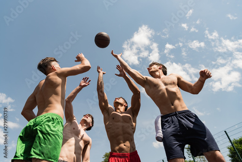 Fotoposter Eigen foto four sexy shirtless sportsmen playing basketball under blue sky
