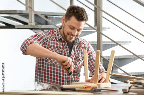 Prime Handsome Working Man Repairing Wooden Stool At Table Indoors Ocoug Best Dining Table And Chair Ideas Images Ocougorg