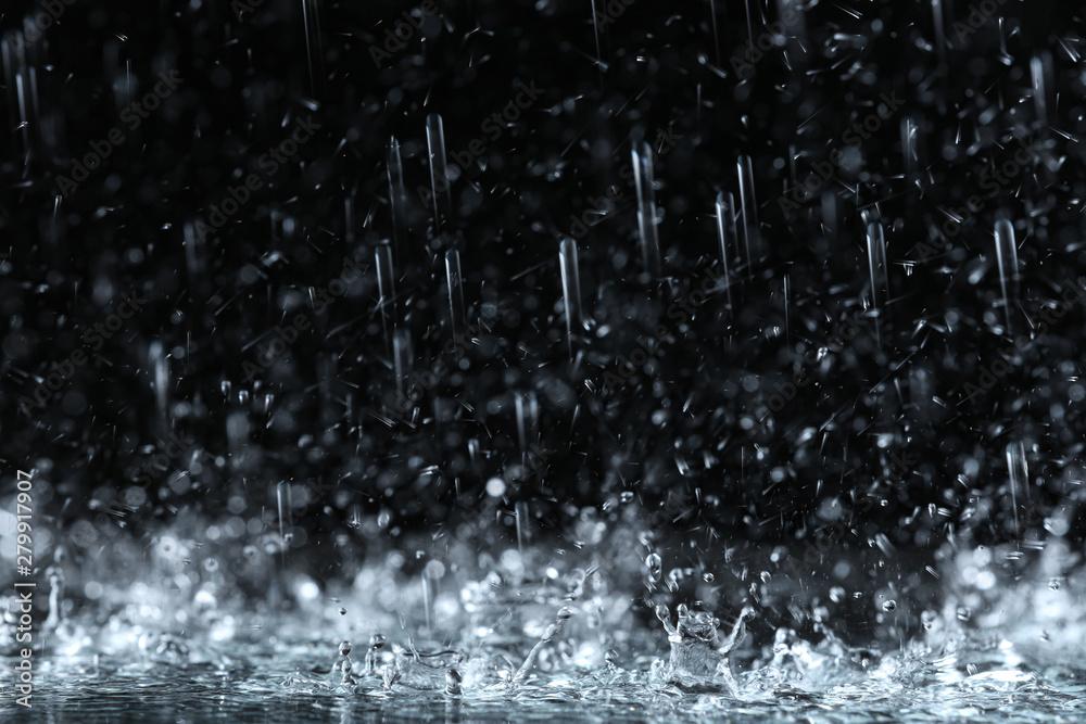 Fototapeta Heavy rain falling down on ground against dark background