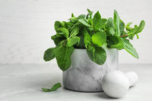 Marble Mortar Full Of Fresh Green Mint On Light Background, Space For Text