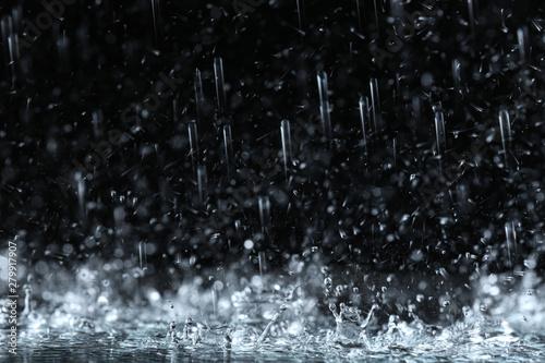 Stampa su Tela Heavy rain falling down on ground against dark background