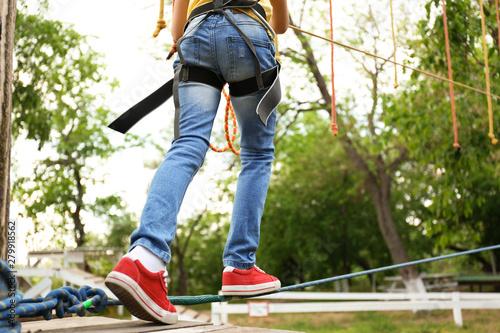 Little girl climbing in adventure park, closeup. Summer camp Poster Mural XXL