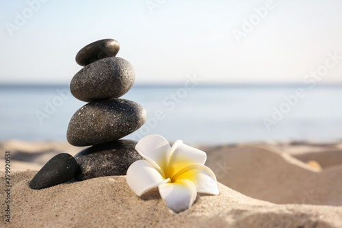 Tuinposter Frangipani Stack of dark stones and beautiful flower on sandy beach near sea, space for text. Zen concept