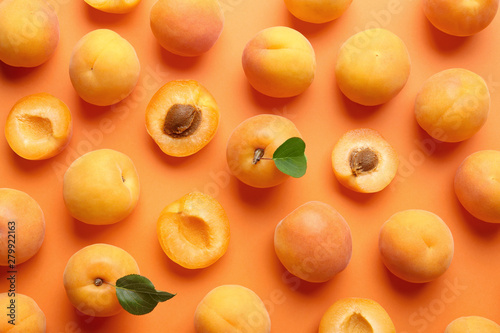 Vászonkép Delicious ripe sweet apricots on orange background, flat lay