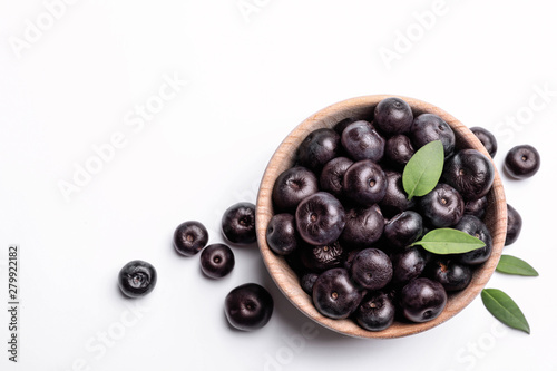 Photo Bowl of fresh acai berries with leaves on white background, top view