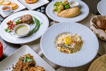 Assorted Food On Table. Spaghetti Carbonara With Bacon, Steak From Beef, Chicken Breast With Broccoli, Greek Salad, Pancakes, Cream Soup Of Pumpkin, Bread, Penne Top View
