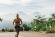 Leinwandbild Motiv Man running topless in uphill on the asphalt road in hot summer weather. Panoramic mountain view on background. Using chest heart rate monitor.