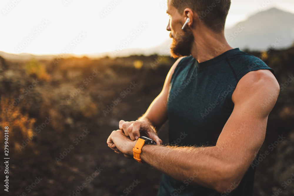 Fototapety, obrazy: Athletic runner start training on fitness tracker or smart watch and looking forward on horizon. Trail running and active lifestyle concept.