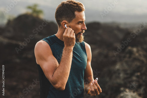 Man using wireless earphones air pods on running outdoors. Active lifestyle concept. - 279940319