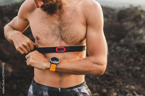 Stampa su Tela Male runner wearing professional chest heart rate monitor and preparing for trail running outdoors