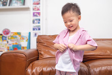 Cute Smiling Little Asian 3 - 4 Years Old Toddler Boy Concentrate On Putting On Shirt ( School Uniform ) At Home, Encourage Self-Help Skills In Children, First Day Of School / Back To School Concept