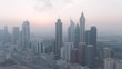 Aerial Drone Footage of the famous Financial District of Dubai, United Arab Emirates along the sheikh zayed road while sunrise with many skyscrapers and the skyline of dubai