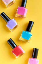 Color Nail Polish Bottles On Yellow Background Composition.