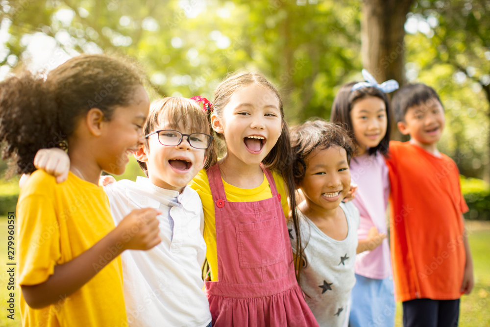 Fototapeta Multi-ethnic group of school children laughing and embracing
